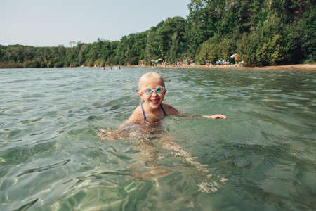 Cute funny Caucasian girl swimming in lake river with underwater goggles. Child diving in water on park beach. Authentic real lifestyle happy childhood. Summer fun outdoor aquatic activity.