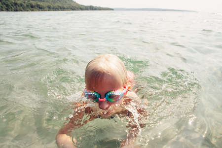 Cute funny Caucasian girl swimming in lake river with underwater goggles. Child diving in water on beach. Authentic real lifestyle happy childhood. Summer fun outdoor aquatic activity. Banco de Imagens