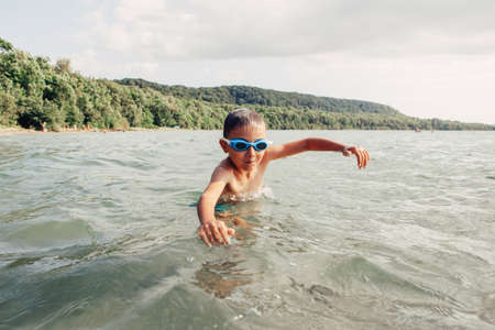 Cute funny Caucasian boy swimming in lake river with underwater goggles. Child diving in water on beach. Authentic real lifestyle happy childhood. Summer fun outdoor aquatic activity.