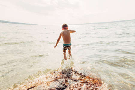 Boy swimming in lake with underwater goggles. Child diving in water with large splash waves. Authentic lifestyle happy childhood. Summer fun outdoor aquatic activity. View from back.