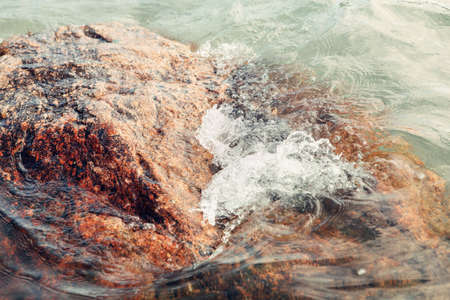Red huge large stone rock in water on beach. Closeup of sea ocean lake wave splash with white foam. Natural background with copyspace.
