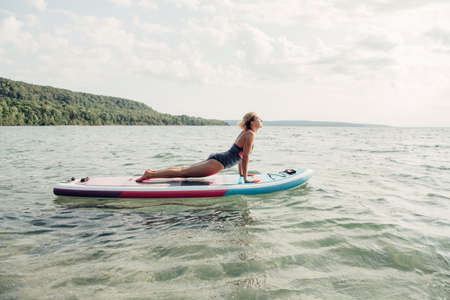 Middle age Caucasian woman practising yoga on paddle sup surfboard at sunset. Female stretching doing workout on lake water. Modern individual hipster outdoor summer sport activity.