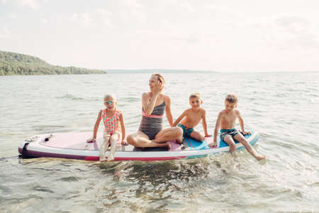 Caucasian woman parent sitting on paddle sup surfboard in water with kids children. Modern outdoor family activity. Individual summer aquatic recreation sport hobby. Healthy lifestyle.