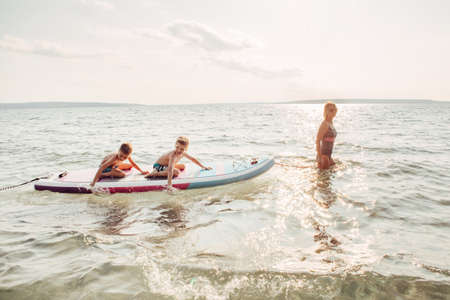 Caucasian woman parent riding kids children boys on paddle sup surfboard in water. Modern outdoor summer fun family activity. Individual aquatic recreation sport hobby. Healthy lifestyle. Banco de Imagens