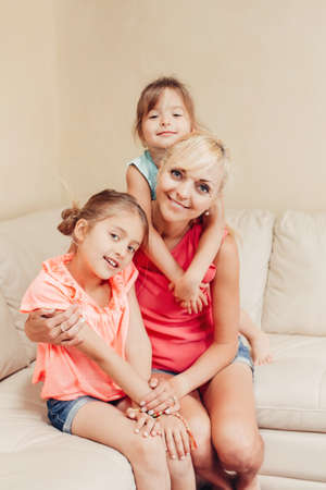 Mother and daughters girls kids at home spending time together. Parent playing with children. Family having fun hugging and laughing. Real people lifestyle.  Mothers day holiday concept. Banco de Imagens