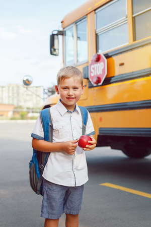 Funny cute happy Caucasian boy student kid with backpack and apple near yellow bus on 1 September day. Education and back to school concept. Child pupil ready to learn and study.
