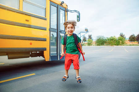 Emotional Caucasian boy student kid with funny face expression jumping near yellow bus on 1 September day. Education and back to school concept. Child pupil ready to learn and study. Banco de Imagens
