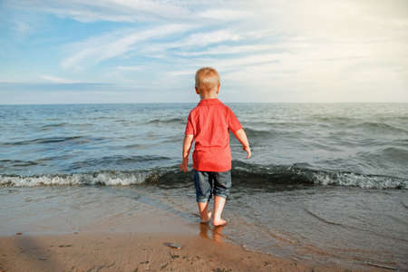 Red-haired toddler child kid in red t-shirt and jeans standing near water on lake sea ocean beach at evening sunset looking far away.  Happy lifestyle childhood concept. View from back. Banco de Imagens