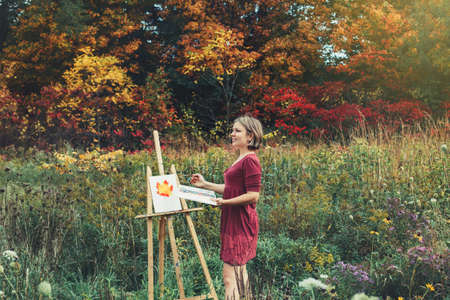 Portrait of young beautiful smiling middle age white Caucasian woman artist drawing in open plein air outside with watercolor on paper at easel.  Lifestyle activity hobby concept