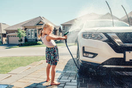 Cute preschool little Caucasian girl washing car on driveway in front house on sunny summer day. Kids home errands duty chores responsibility concept. Child playing with hose spraying water. 스톡 콘텐츠