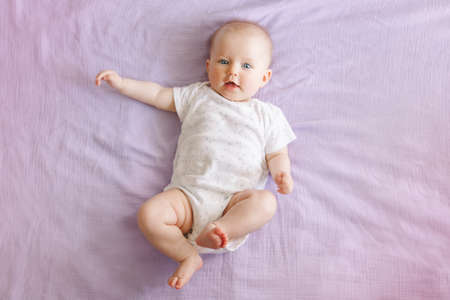 Portrait of cute adorable smiling white Caucasian baby girl boy with blue eyes four months old lying on bed looking at camera. View from top above. Happy childhood lifestyle. Stock fotó