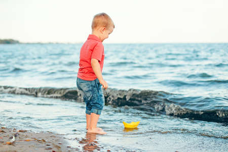 Happy Caucasian red-haired toddler child boy putting yellow paper boat in water on lake sea ocean shore at evening sunset or morning. Kid playing on beach. Happy lifestyle childhood concept.