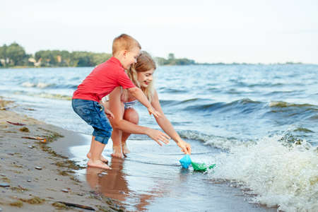 Caucasian mother with toddler son child putting paper boats in water together on lake shore. Kid playing on beach. Outdoor family summer activity. Happy lifestyle childhood.