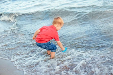 Happy Caucasian red-haired toddler child boy putting blue paper boat in water on lake sea ocean shore at evening sunset or morning. Kid playing on beach. Happy lifestyle childhood concept.