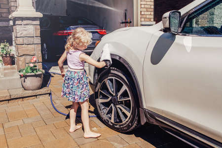 Cute preschool little Caucasian girl child washing cleaning car and wiping glass window on driveway in front house on sunny summer day. Kids home errands duty chores responsibility concept.