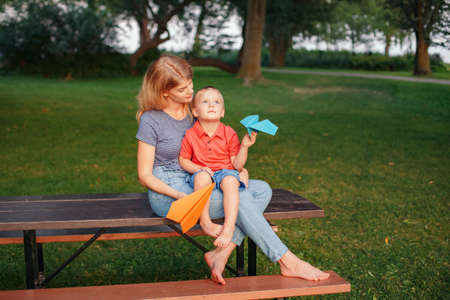 Dreaming of future. Mom and son playing with colored paper airplanes. Caucasian mother and boy toddler sitting together on wooden bench. Happy family childhood lifestyle.