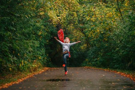 Funny cute adorable Caucasian preschool girl playing with red scarf in autumn fall park. Child running jumping outside in street road. Happy authentic childhood lifestyle. Outdoor activity for kids.