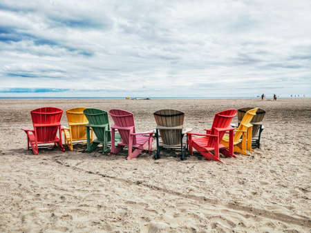 Eight many colorful red, brown and yellow wooden muskoka Adirondack chairs in row on beach outside. Concept of relaxation and calm talk conversation among friends or family.