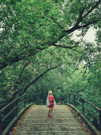 Portrait of one cute adorable preschool girl walking in park on bridge outdoor in forest. Lost abandoned child kid in empty wild nature place.