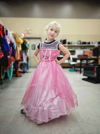 Cute adorable girl trying on costume pink fairy dress in store for Halloween holiday celebration. Happy funny kid in supermarket second hand.