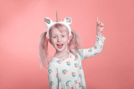 Cute adorable smiling Caucasian blonde girl in white dress with unicorn headband horn on pink coral background. Funny kid child expressing emotion and pointing showing with finger.