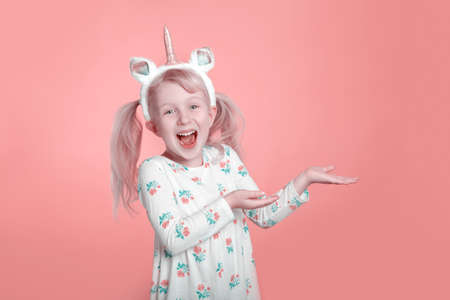 Cute adorable smiling Caucasian blonde girl in white dress wearing unicorn headband horn in studio on coral pink background. Funny kid child expressing emotion and showing pointing.