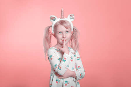 Cute adorable Caucasian blonde girl in white dress wearing unicorn headband horn and ears thinking dreaming. Funny kid child expressing emotion standing in studio on pink coral background.
