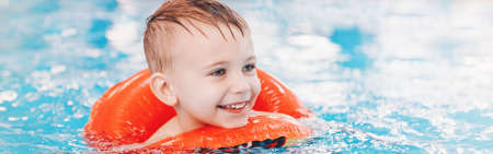 Portrait of happy smiling Caucasian child in swimming pool. Preschool boy training to float with red circle ring in water. Web banner header for website. Healthy active lifestyle childhood. Banco de Imagens