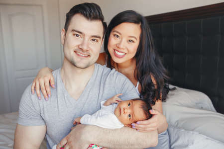 Beautiful smiling Chinese Asian mother and Caucasian father with newborn infant baby child. Happy family together in bedroom. Home lifestyle authentic natural moment. Positive emotions.