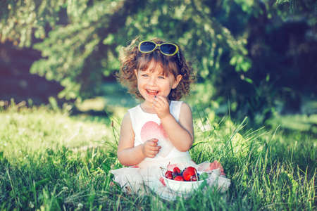 Cute adorable Caucasian toddler baby girl sitting on grass and eating berries fruits. Funny child with sunglasses in park having healthy snack meal. Summer delicious tasty finger food for kids. Stock Photo