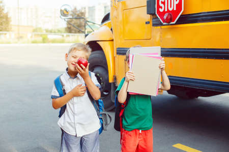 Two funny happy Caucasian boys students kids with apples standing near yellow bus on 1 September day. Education and back to school concept. Children pupils ready to learn and study.