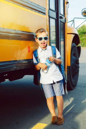 Funny cute happy Caucasian boy student kid with backpack and water bottle near yellow bus on 1 September day. Education and back to school concept. Child pupil ready to learn and study.