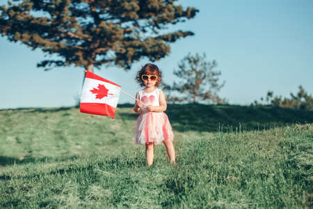 Portrait of adorable cute little Caucasian baby toddler girl standing on green grass in park outside and holding waving large Canadian flag. Kid child citizen celebrating Canada Day on 1st of July.