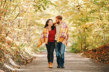Beautiful couple man woman in love. Smiling laughing boyfriend and girlfriend wrapped in yellow blanket walking in park on autumn fall day. Togetherness and happiness. Authentic real people. Stok Fotoğraf
