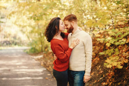 Portrait of beautiful couple man woman in love. Boyfriend and girlfriend hugging kissing outdoor in park road on autumn fall day. Togetherness and happiness. Authentic real people feelings.