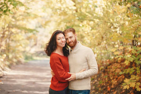 Portrait of beautiful couple man woman in love. Boyfriend and girlfriend hugging tender outdoor in park on autumn fall day. Togetherness and happiness. Authentic real people relationships.