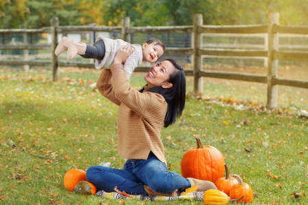 Happy smiling laughing Asian Chinese mother with cute adorable funny baby girl sitting in autumn fall park outdoor with yellow orange pumpkins. Stok Fotoğraf