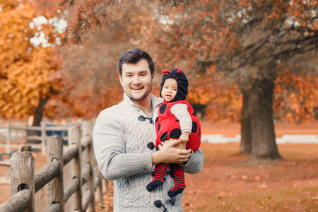 Happy smiling Caucasian father dad with cute adorable baby girl in ladybug costume. Family in autumn fall park outdoor with yellow orange leaves trees. Halloween seasonal concept.