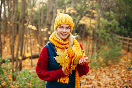 Portrait of beautiful Caucasian happy smiling woman wearing yellow scarf and hat in autumn fall park. Person looking at camera and holding yellow fallen autumnal leaves. Seasonal activity lifestyle.  Stok Fotoğraf