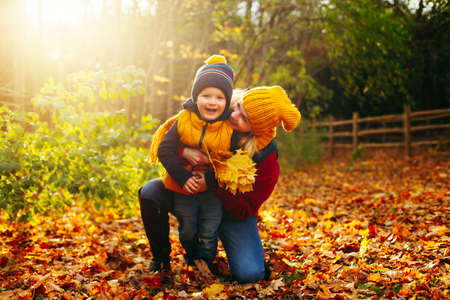Caucasian young mother hugging playing with cute adorable toddler boy son in autumn fall park outdoor with yellow orange leaves trees. Thanksgiving autumnal seasonal concept.  Stok Fotoğraf