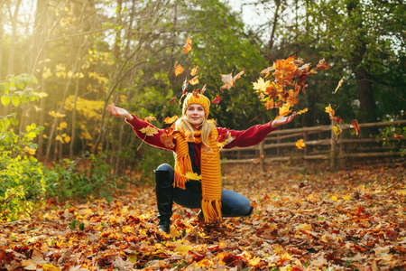 Portrait of beautiful Caucasian happy smiling woman girl in warm yellow scarf and hat throwing autumn fall orange red leaves in park forest outdoor. Seasonal activity lifestyle outside.  Stok Fotoğraf
