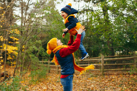 Caucasian young mother playing throwing up in air cute funny adorable toddler boy. Mom and son having fun in autumn fall park with yellow leaves. Family lifestyle activity outdoor.  Stok Fotoğraf