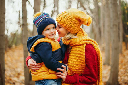 Caucasian young mother hugging talking to cute adorable toddler boy son in autumn fall park outdoor with yellow orange red tree leaves. Happy family. Autumnal seasonal activity outdoor.