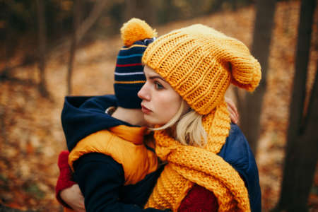 Mother in yellow hat scarf hugging pacifying sad upset crying toddler boy son in autumn fall park outdoor. Bonding relationship of mom and child baby. Family together protection.
