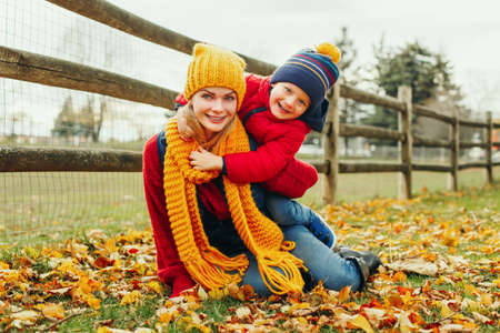 Caucasian young mother sitting on ground hugging cute adorable toddler boy son in autumn fall park outdoor with yellow orange red leaves. Thanksgiving autumnal seasonal family activity.