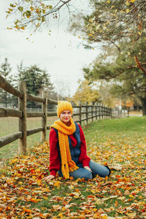 Portrait of beautiful Caucasian happy smiling woman looking at camera in yellow scarf and hat sitting on ground in autumn fall park farm in red orange green fallen leaves. Seasonal activity lifestyle.