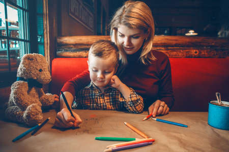 Portrait of young Caucasian mother and son sitting in restaurant drawing with colored pencils on craft brown paper. Family together in cafe. Lifestyle authentic real people. Toned with filters.