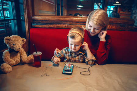 Portrait of young blonde Caucasian mother with toddler boy son sitting in cafe restaurant and playing electronic digital gadget device toy