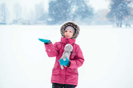 Cute adorable funny Caucasian smiling girl child in warm clothes red pink jacket playing with snow catching snowflakes during cold winter snowy day.