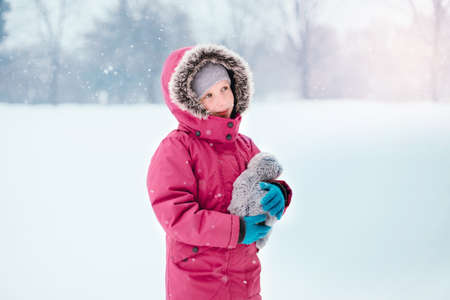 Cute adorable Caucasian smiling girl child in warm clothes red pink jacket playing looking at  falling snow snowflakes during cold winter snowy day. Kids outdoor seasonal activity. Stok Fotoğraf